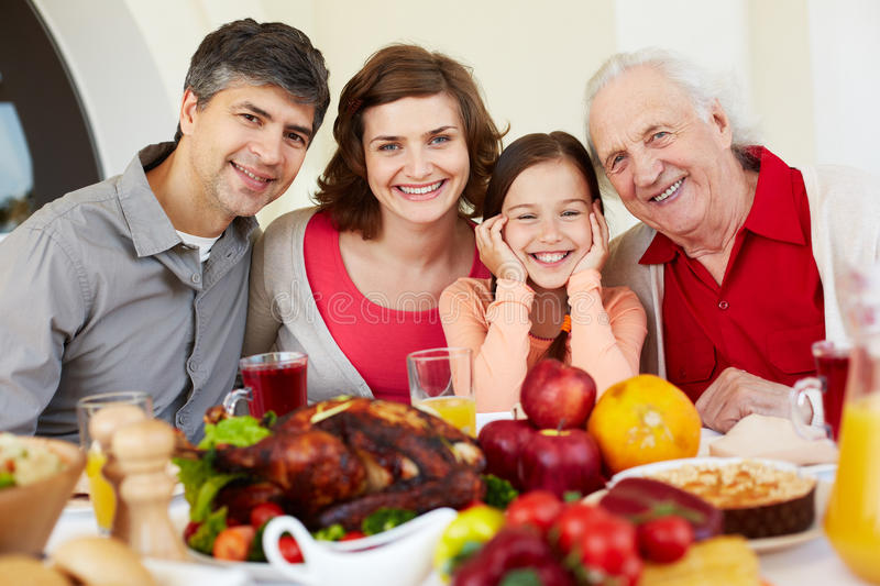 Happy family holiday. Family of four gathering for dinner royalty free stock photography