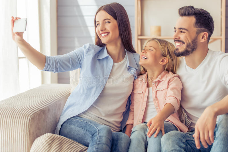 Happy family at home. Beautiful young mother, father and their daughter are making selfie using a phone and smiling while sitting on the sofa at home royalty free stock photo