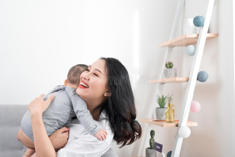 Happy family at home. Mother holding baby daughter in living room in cozy weekend morning royalty free stock photography