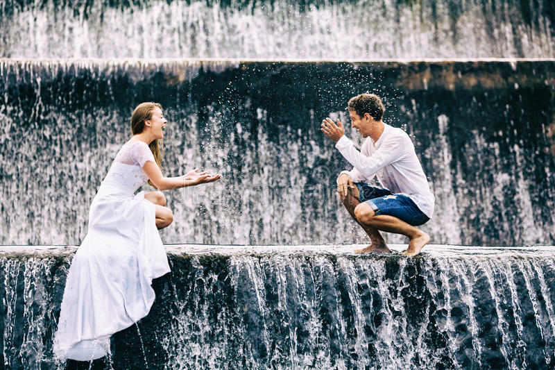 Happy family honeymoon holiday. Couple in cascade waterfall pool. royalty free stock images