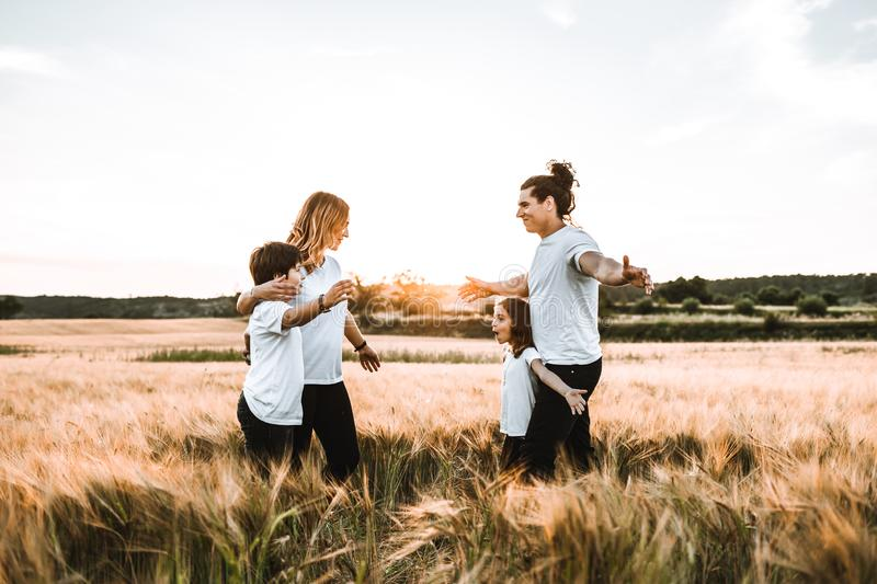Happy family hugging in the field and smiling. Family in a sunset royalty free stock photos