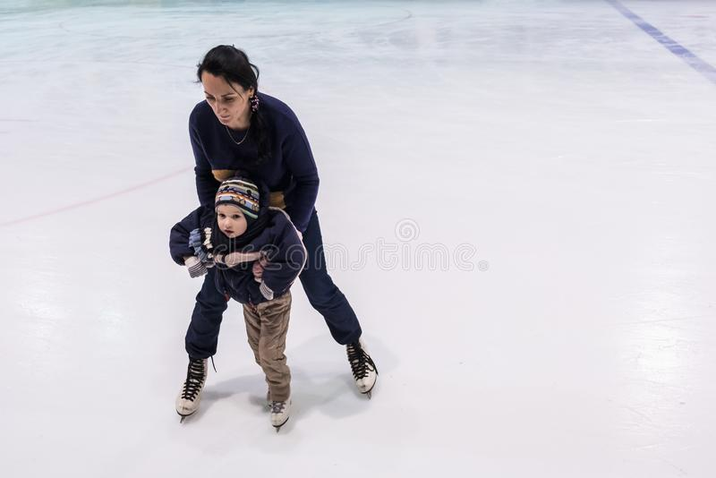 Happy family indoor ice skating at rink. Teaching studying baby child. stock images