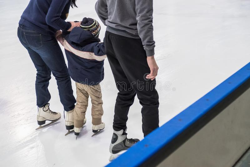 Happy family indoor ice skating at rink. Winter royalty free stock image