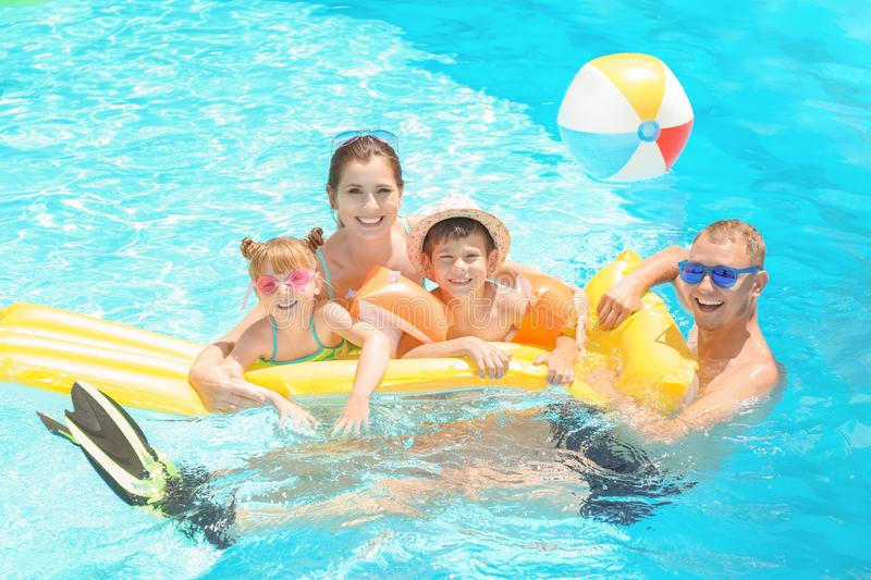 Happy family with inflatable mattress in swimming pool royalty free stock photography
