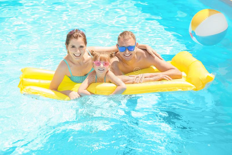 Happy family with inflatable mattress in swimming pool stock images