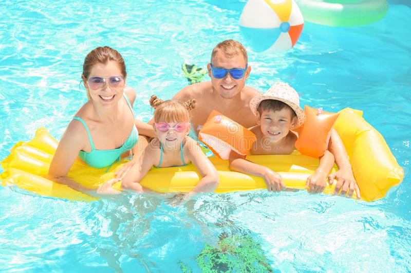 Happy family with inflatable mattress in swimming pool stock photos