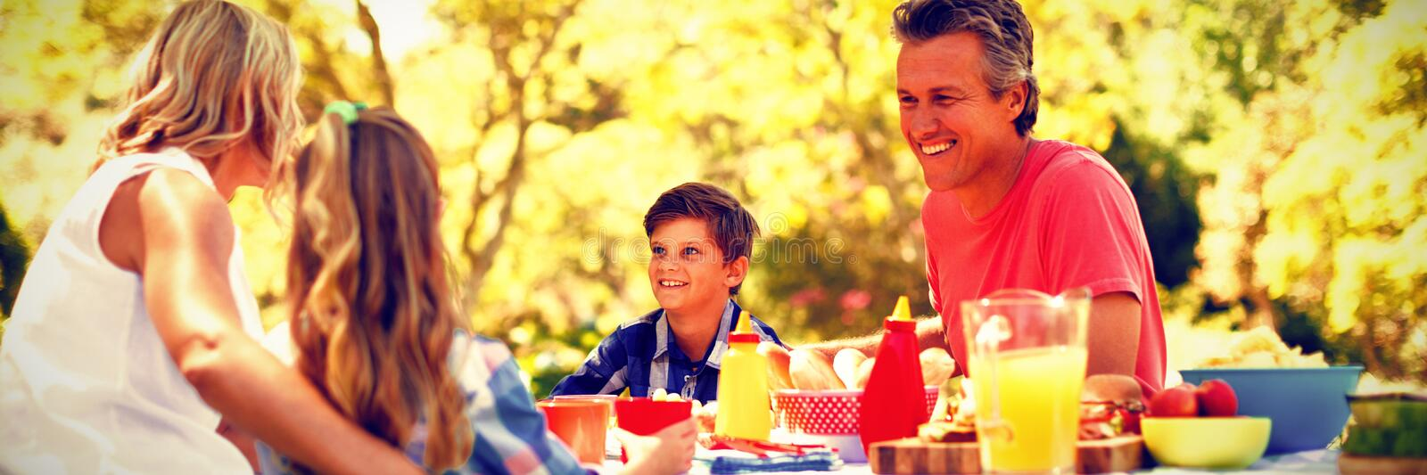 Happy family interacting with each other while having meal in park stock image