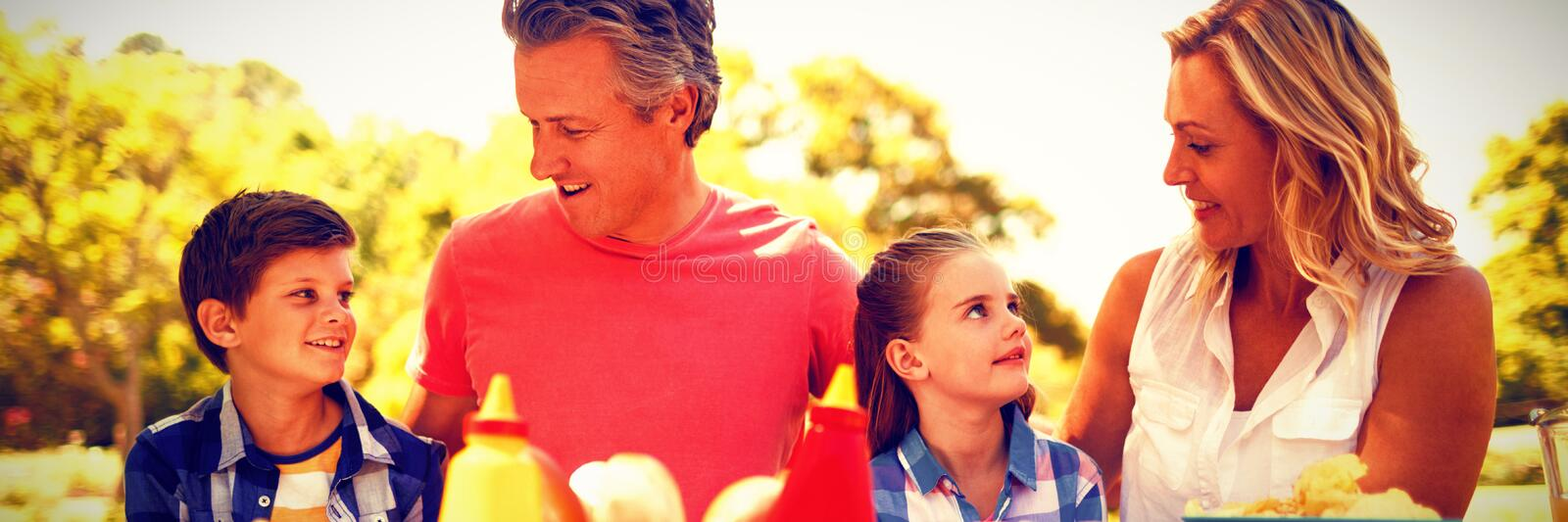 Happy family interacting with each other while having meal in park stock images