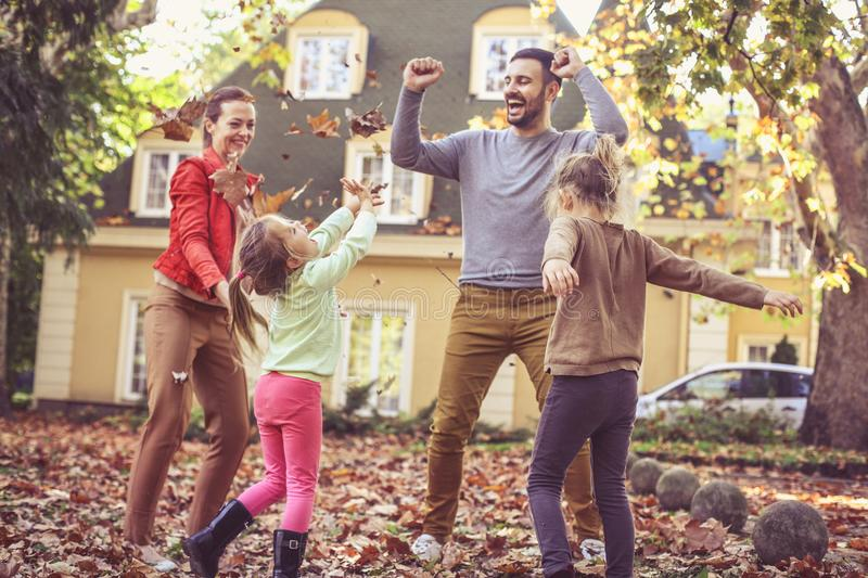 Happy family jumping at backyard. Fall leaves is fun. royalty free stock photo