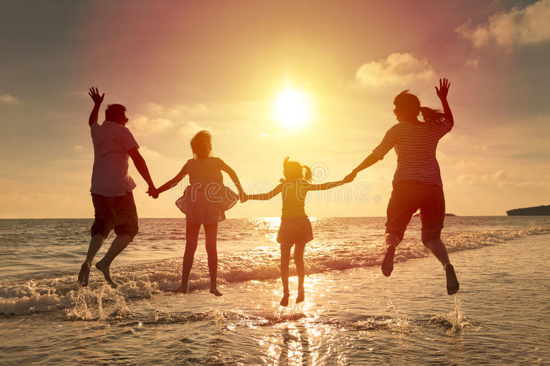 Happy family jumping on the beach royalty free stock photography