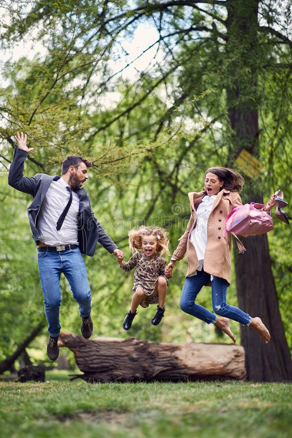 Happy family jumping in park after school and work royalty free stock image