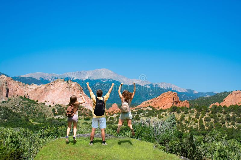 Happy family jumping with raised hands on vacation hiking trip. stock photography