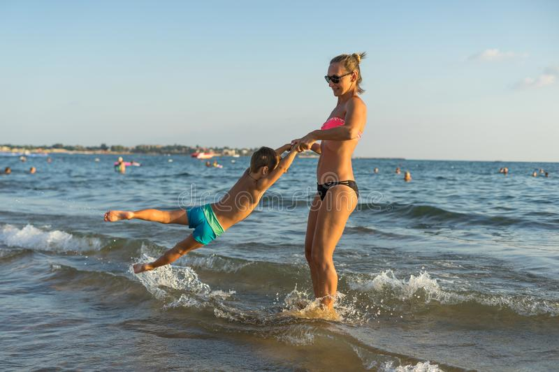 Happy family jumping together on the beach - Image stock photos