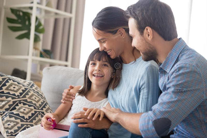 Happy family with kid cuddle on couch congratulating with birthday. Happy young family with kid embrace sit on couch with gift box in hands, smiling mom and dad stock image