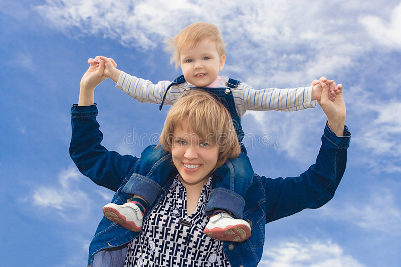 Happy family kid sit on neck. Over blue sky royalty free stock image