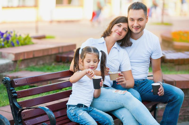 Family kidding in the city, sitting on a bench and eating ice cream stock image