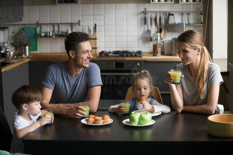 Happy family and kids having breakfast sitting at kitchen table. Smiling mom and dad eating together with children talking enjoying tasty food fresh juice and stock photo