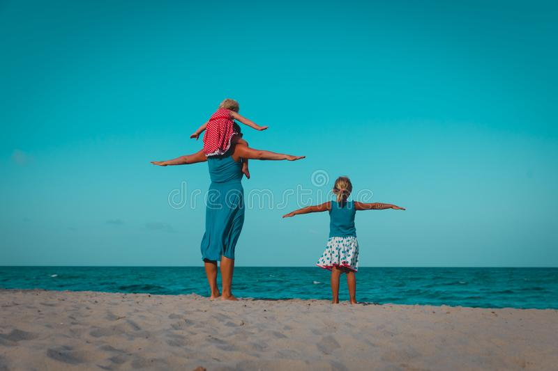 Happy family with kids play on beach, mom with daughters fly at sea stock photography