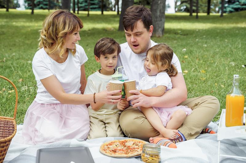 Happy family with kids resting on the grass during a picnic. Happiness and harmony in family life royalty free stock image