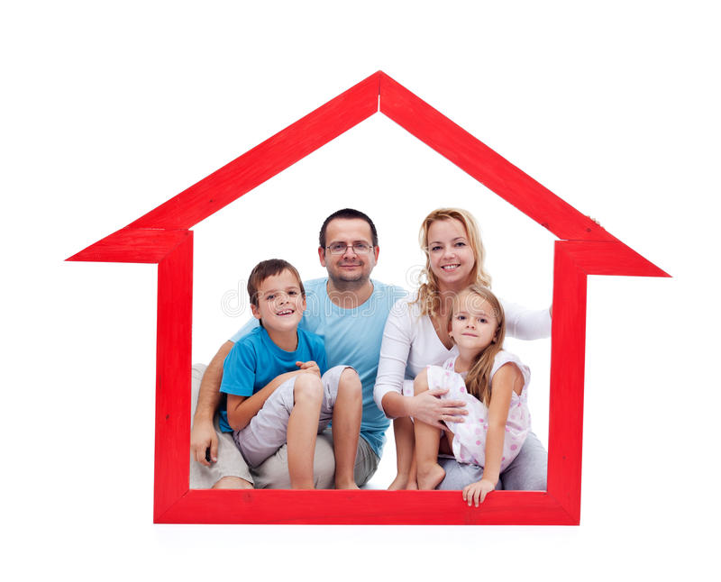 Happy family with kids in their home concept. Sitting in a house shaped frame - isolated royalty free stock photography