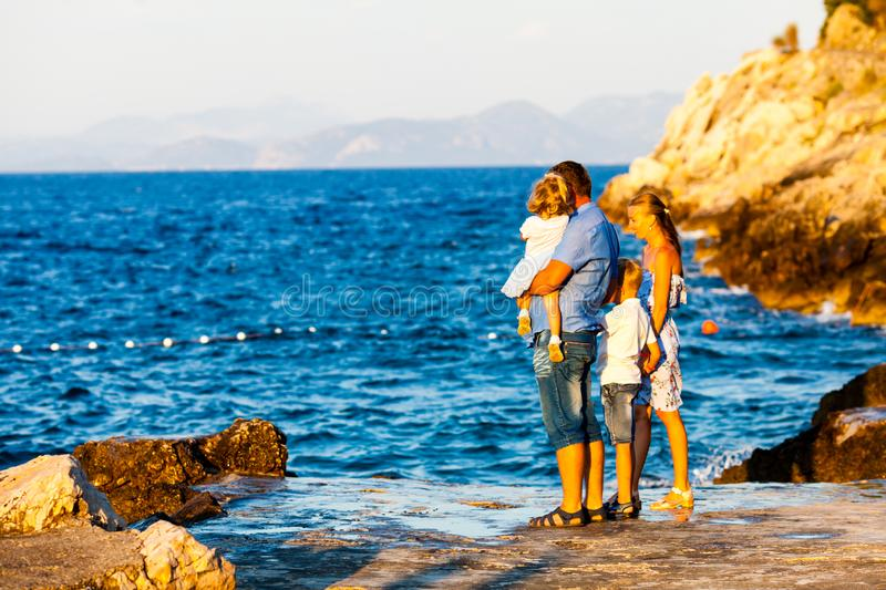 Happy family with kids walk at sunset rocks. Mother and father with kids walk on beach on the sunset, family vacation stock photo