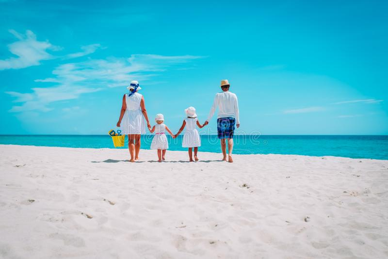 Happy family kids walk on tropical beach vacation. Mom, dad and two little daughters at sea stock photography