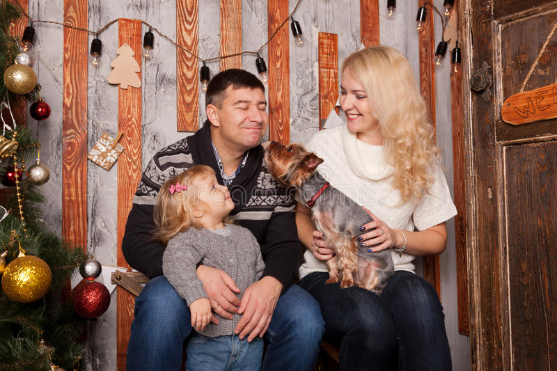 Happy family kissing with dog at home. royalty free stock photo