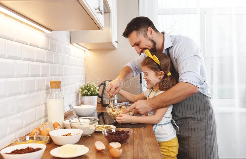 Happy family in kitchen. Father and child daughter knead dough a. Nd bake the biscuits together royalty free stock photos