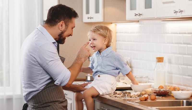 Happy family in kitchen. father and child baking cookies. Happy family in kitchen. Father and child son baking cookies together royalty free stock photography