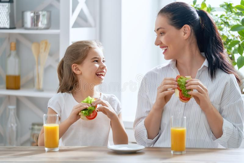 Happy family in the kitchen. Healthy food at home. Happy family in the kitchen. Mother and child daughter are having breakfast royalty free stock image