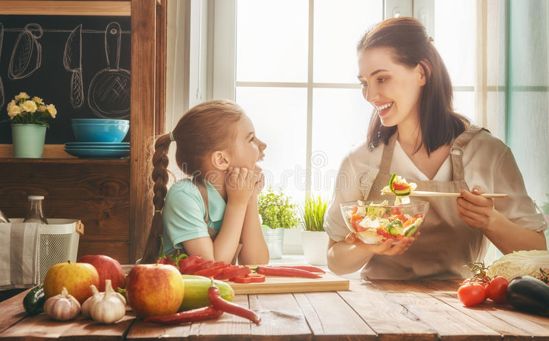 Happy family in the kitchen. Healthy food at home. Happy family in the kitchen. Mother and child daughter are preparing the vegetables and fruit royalty free stock photo