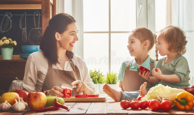 Happy family in the kitchen. Healthy food at home. Happy family in the kitchen. Mother and children daughters are preparing the vegetables and fruit royalty free stock photo