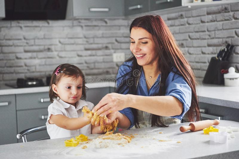 Happy family in the kitchen. Holiday food concept. Mother and daughter preparing the dough, bake cookies. Happy family stock images