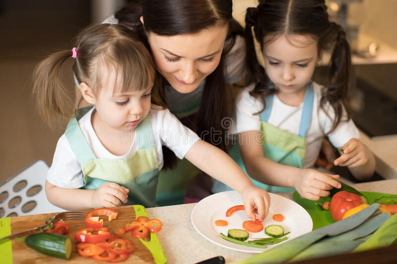 Happy family in the kitchen. Mom and daughters playing and having fun in the kitchen preparing. stock images