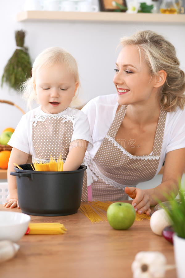 Happy family in the kitchen. Mother and child daughter cooking pasta stock photo