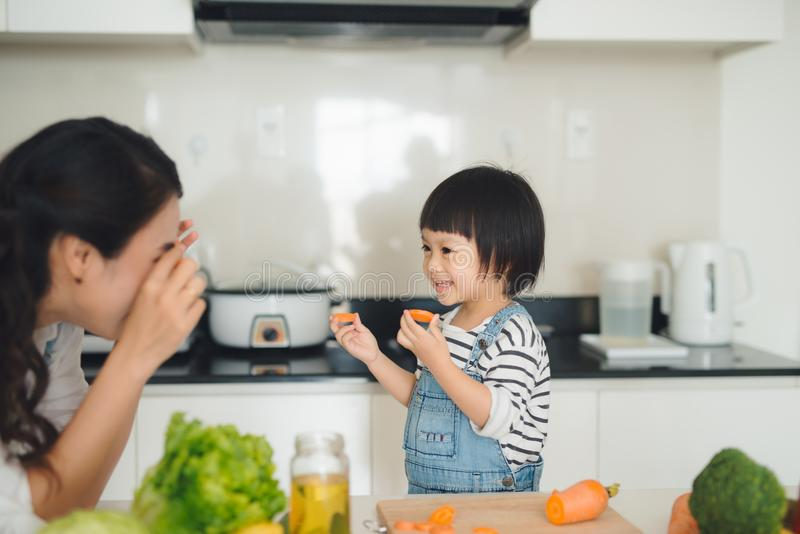 Happy family in the kitchen. Mother and child daughter are preparing the vegetables and fruit. royalty free stock image