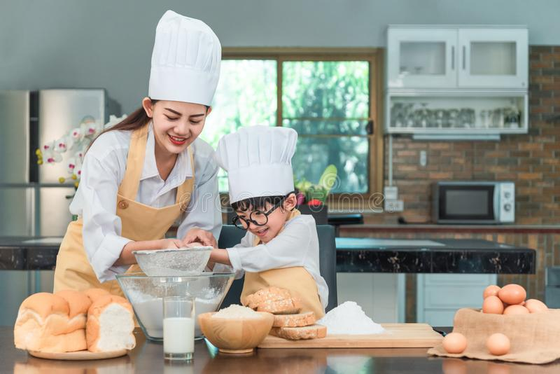 Happy family in the kitchen. mother and child daughter preparing the dough, bake cookies stock photography