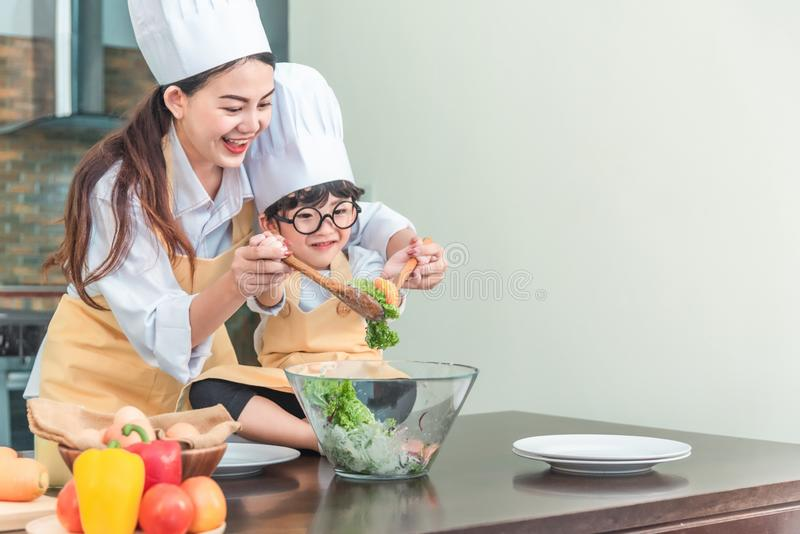 Happy family in the kitchen. mother and child daughter preparing the dough, salad royalty free stock images