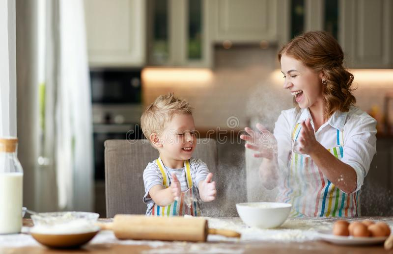 Happy family in kitchen. mother and child preparing dough, bake cookies. Happy family in the kitchen. mother and  child son preparing the dough, bake cookies stock images