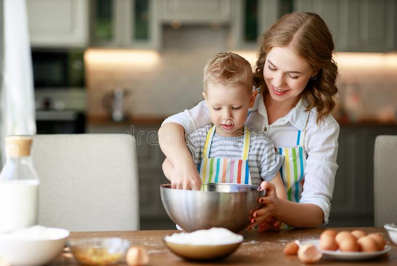 Happy family in kitchen. mother and child preparing dough, bake cookies royalty free stock image