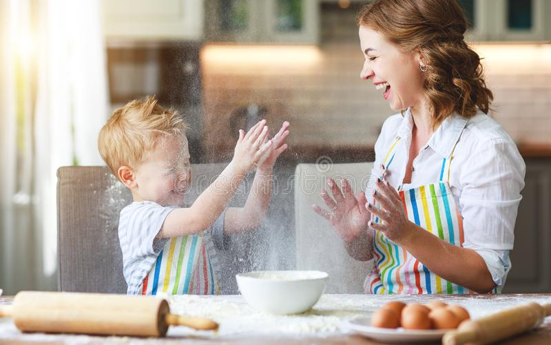 Happy family in kitchen. mother and child preparing dough, bake cookies stock photography
