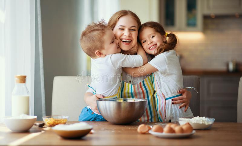 Happy family in kitchen. mother and children preparing dough, bake cookies. Happy family in the kitchen. mother and  children preparing the dough, bake cookies royalty free stock photo