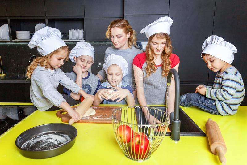 Mother and children cooking in kitchen and having fun. Happy family in kitchen. Mother and five children preparing dough, bake apple pie. Mom, daughters and sons royalty free stock photo