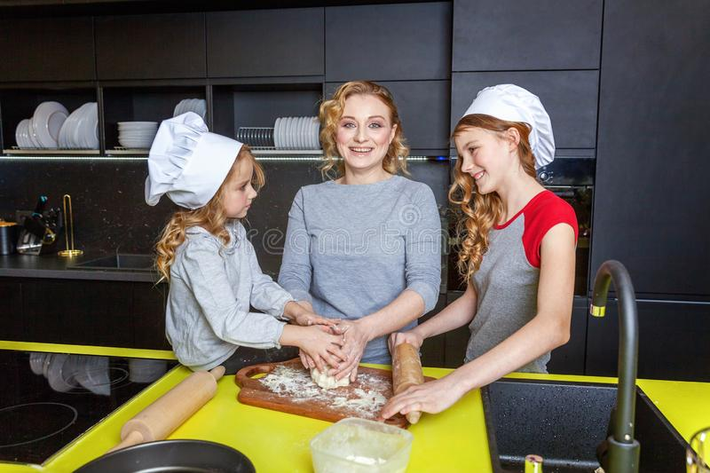 Mother and children cooking in kitchen and having fun. Happy family in kitchen. Mother and two children preparing dough, bake apple pie. Mom and daughters royalty free stock photos