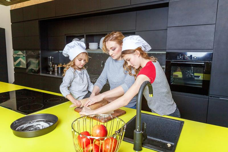 Mother and children cooking in kitchen and having fun. Happy family in kitchen. Mother and two children preparing dough, bake apple pie. Mom and daughters royalty free stock image