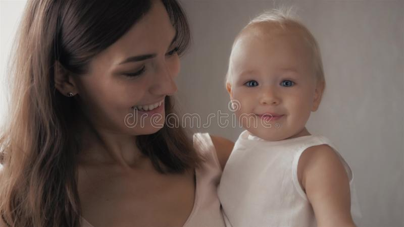 Happy family laughing faces, mother holding adorable child baby boy, smiling and hugging, close up border, beauty of stock images