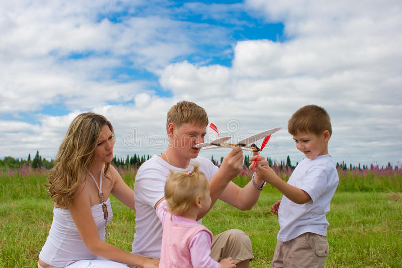 Happy family launching toy aircraft model together royalty free stock image