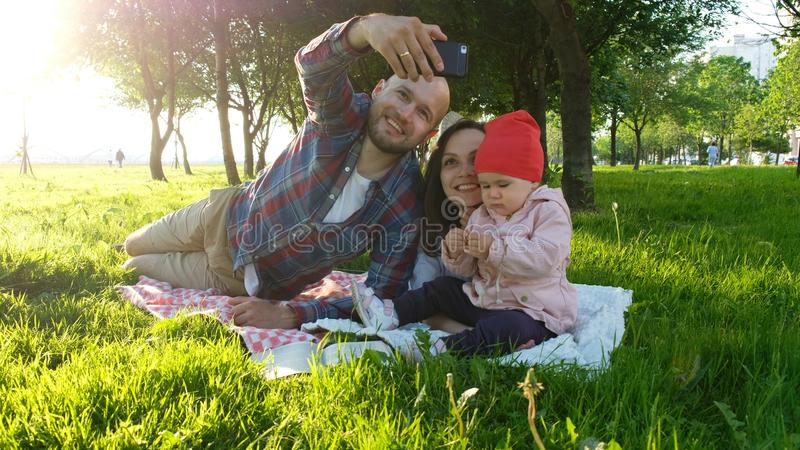 Happy family is laying on the grass and father doing selfie with a baby at sunset in the park on the smartphone royalty free stock photos