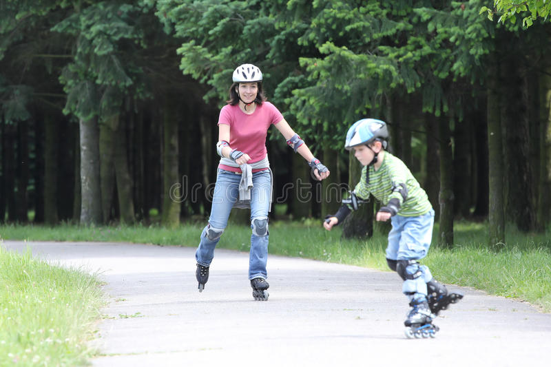 Happy family learning to ride on rollerblades. 6 years old boy and his mother learning to ride on rollerblades in the park royalty free stock photography