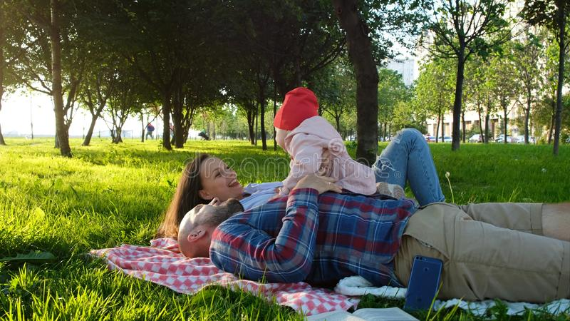 Happy family lies on the grass and plays with the child at sunset in the park stock photo